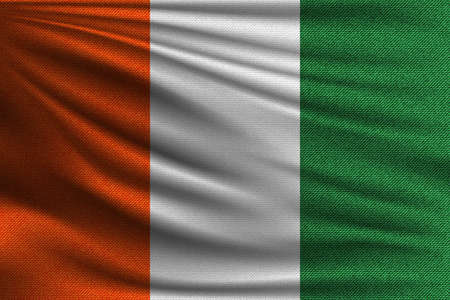 The national flag of Ivory coast. The symbol of the state on wavy cotton fabric. Realistic vector illustration.