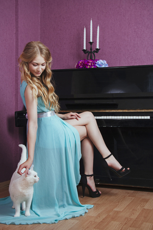 sexy beautiful blonde girl in dress playing piano with a cat Stock Photo
