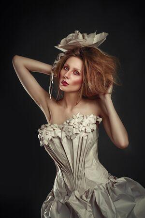 Beautiful redhead girl in elegant paper dress. Sensual image with bright makeup. Beauty model Stock Photo