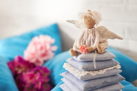 Little angel doll sitting on a pillow. Valentines day. Childrens toy hand made