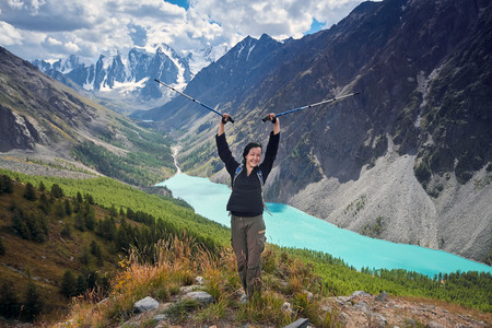 Brave girl conquering mountain peaks of the Altai mountains. The majestic nature of the mountain peaks and lakes. Hiking in rugged places. Journey through Russia, Siberia, Aktru and shavlinskoe lake