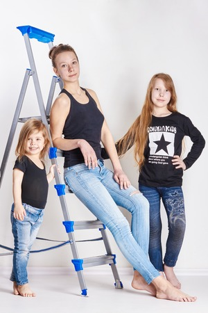 illustrative: Russia Ekaterinburg - April 1, 2017: Three girls posing, a model school for children. Fashion art fashion. Sisters together on a light background. Bright summer clothes Editorial