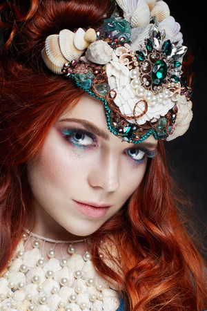 Redhead girl with bright makeup and big lashes. Mysterious fairy woman with red hair. Big eyes and colored shadows, long lashes. Sexy look, pure skin care, care face