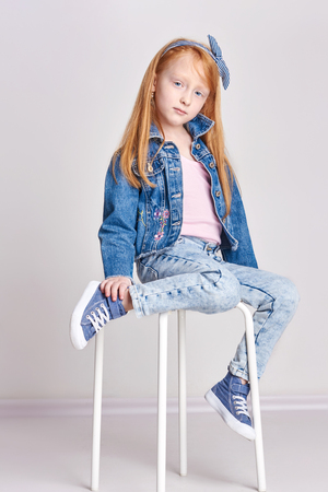 illustrative: Russia Ekaterinburg - April 1, 2017: Little girl with red hair, beautiful long hair. Redhead child posing on a light background, fashion model school. Joy and fun