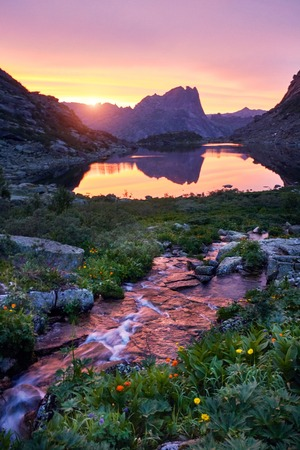 Sunset in mountains near river. Sunlight reflected on mountain tops. Golden light from sky reflected in a mountain river. Ergaki