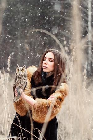 Frau im Herbst in Pelzmantel mit Eule auf der Hand ersten Schnee. Schöne Brünette Mädchen mit langen Haaren in der Natur, mit einer Eule. Romantische, zarte Mädchen Standard-Bild - 84256154