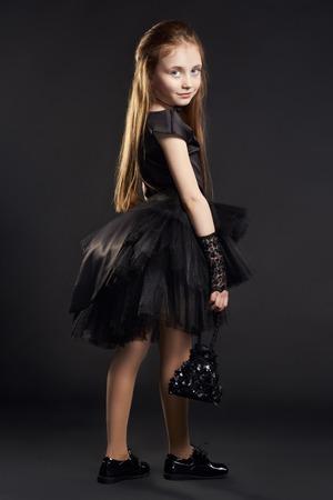 검정색 배경에 검은 가방 검은 드레스에 어린 소녀. 소녀는 할로윈 휴가를 준비하고 있습니다. 스톡 콘텐츠