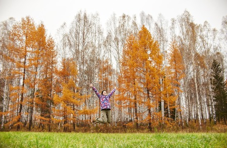 Woman rejoices at the arrival of autumn. Girl in a field near the yellow autumn forest, autumn came, the emotion of joy. Golden yellow trees in the forest. Birch grove