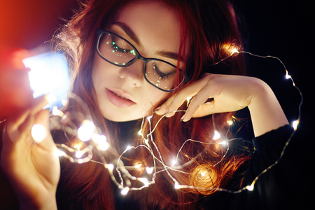 Art portrait of a woman with red hair in Christmas lights. Girl in glasses with reflected Christmas lights. Red hair in a yellow lights, tender feelings. Christmas came