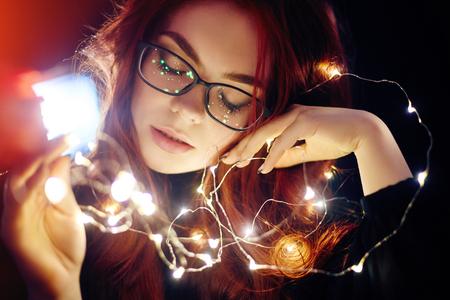 Kunstportret van een vrouw met rood haar in Kerstmislichten. Meisje in glazen met weerspiegelde Kerstmislichten. Rood haar in een geel licht, tedere gevoelens. Kerstmis kwam