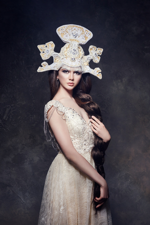 Art Woman with a long braid in a luxurious long dress and fabulous headpiece. Girl snow Queen posing on a dark background. Portrait of a woman fairy Stock Photo