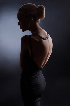 Contrast fashion woman portrait on dark background, the silhouette of a girl with a beautiful curved back. Naked back of a woman in the dark. Luxury blonde posing in evening dress
