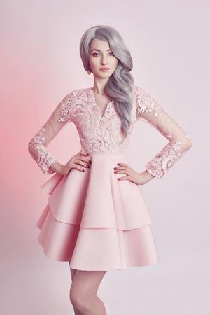 Piękna dziewczyna lalka anime w różowej sukience na różowym tle. Dziewczyna z długimi blond popielatymi włosami. Wspaniały wygląd kobiecej bohaterki anime