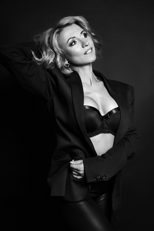 Portrait of sexy business women blonde in a black jacket, bare body, perfect figure girls, erotic sensual look, daring image, the woman in black . Body and face skin care, hydration and nutrition