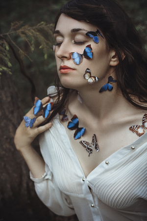 Beautiful art portrait of a naked woman with blue butterflies on her face and hands near the branch of spruce in nature in the forest. Mysterious magical romantic view of girl near the tree branches