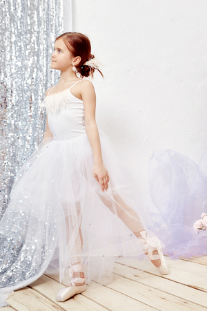 Little prima ballet. Young ballerina girl is preparing for a ballet performance. Girl in a white ball gown and Pointe near the window, beautiful red hair. Young theater actress Stock Photo