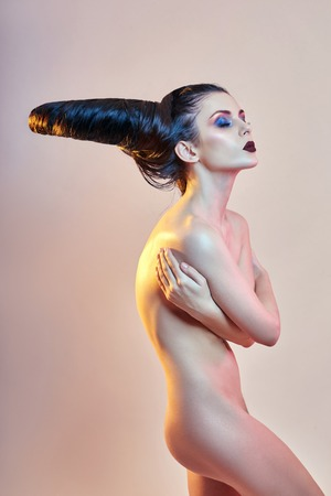 Nude art woman with hair in the form of horns, a female demon with bright makeup, perfect body girl, the horns on the head. Devil in feminine guise, Halloween. Hairstyle hair brunette Stockfoto