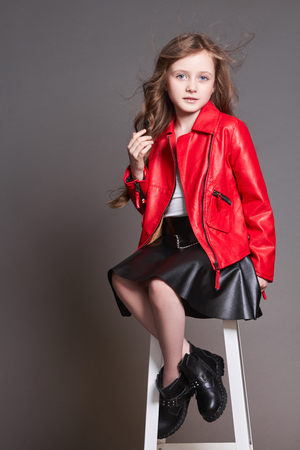 Fashion child girl in red leather jacket and black skirt posing near the stool in the Studio. Spring clothes to be a trend of fashion, the young model is on a gray background Foto de archivo