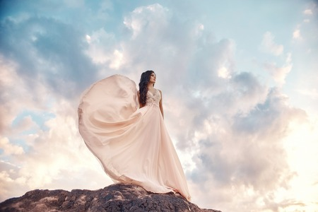 Gorgeous woman brunette in the mountains at sunset and blue sky with clouds. The woman looks into the distance in a long white dress developing in the wind. Summer sun sky nature vacation 스톡 콘텐츠