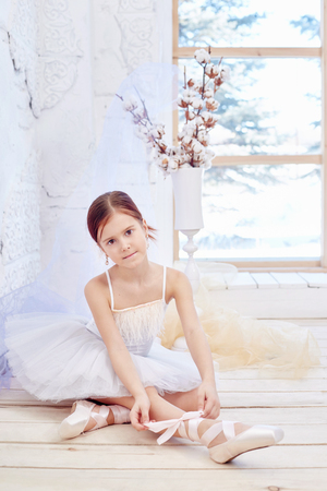 Little prima ballet. Young ballerina girl is preparing for a ballet performance. Girl in a white ball gown and Pointe near the window, beautiful red hair. Young theater actress Standard-Bild