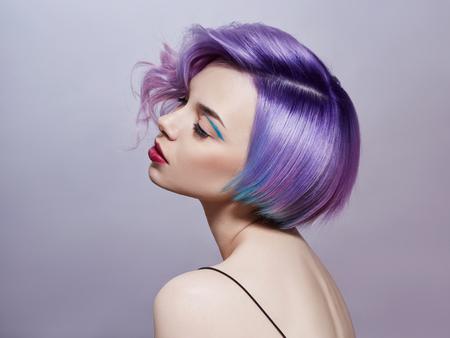 Porträt einer Frau mit bunten fliegenden Haaren, alle Schattierungen von Purpur. Haarfärbung, schöne Lippen und Make-up. Haare flattern im Wind. Sexy Mädchen mit kurzen Haaren. Professionelle Färbung
