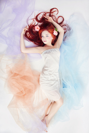 Romantic woman with long hair and cloud dress. Girl dreaming bright makeup and perfect body. Redhead girl in light airy colored dress lies on the floor white background. Beautiful flowers in girl hair