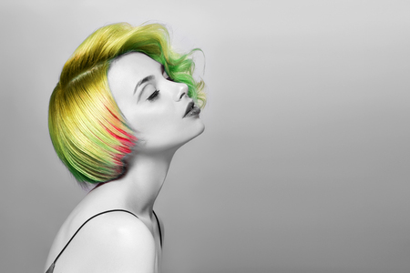 Portrait of a woman with bright colored flying hair, all shades of green. Hair coloring, beautiful lips and makeup. Hair fluttering in the wind. Sexy girl with short hair. Professional coloring