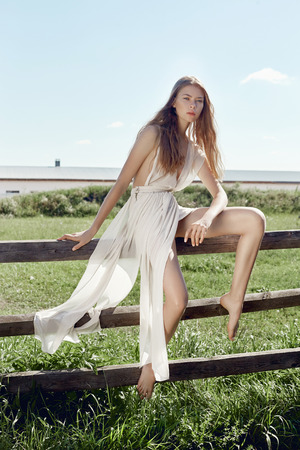 Sexy young fashion woman in light white dress posing sitting on a wooden fence in the field. Girl with a perfect figure on the background of a rural landscape Banque d'images