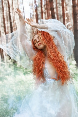 Beautiful redhead woman forest nymph in a blue transparent light dress in the woods spinning in dance. Red hair girls. Art fashion portrait of fairy woman fairy tale in summer forest Stock fotó