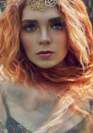 Beautiful redhead Norwegian girl with big eyes and freckles on face in the forest. Portrait of redhead woman closeup in nature, fabulous mysterious appearance long wavy red hair in the sun. Hair care 免版税图像