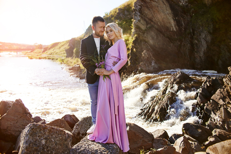 Beautiful young couple hugs and looks away and at each other enjoying a romantic date on the river. Man and woman standing on the rocks in the sun near the sea at sunset Banco de Imagens
