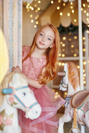 Beautiful red-haired girl with long hair and blue eyes rides a carousel in a long pink dress. Carousel in the form of horses, redhead girl celebrates her birthday in the amusement Park 免版税图像