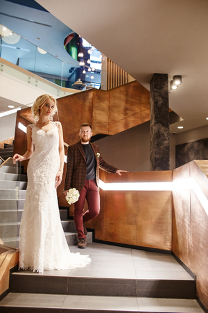 Bride in a chic long dress with a train and the groom stand on big stairs, couple in love hugs on stairs kiss and look at each other. Day of the wedding, couple on the day of registration of marriage Stock Photo