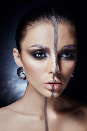 Creative makeup on woman face, beautiful big eyes. Fashion Perfect makeup, silver color band on the girl face, silver eyebrows and black brunette hair. Portrait of a woman on a dark background