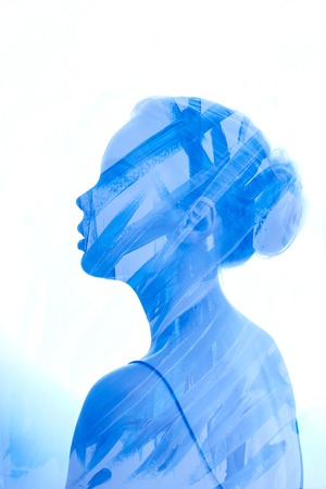 Art Portrait woman consisting of brush strokes of blue paint on a white background. Paint on girl face, fashion beauty and makeup. Double exposure, no focus. The mysterious portrait streaks blue paint