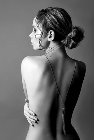 Art of Nude fashion Nude back blonde on grey background, pendant necklace on chain on back. Beauty and skin care perfect body. Girl hugs her hands Standard-Bild - 118895381