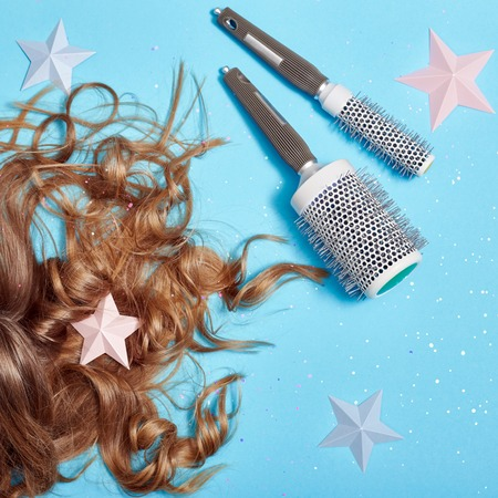Hair care, long beautiful hair and comb, combing, strong healthy roots. Hair lying on blue background. Hairdresser and accessories, perfect hairstyle. Top view, hairdresser table