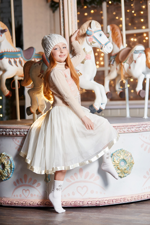 Bright red-haired little girl in a white hat and a beautiful dress is sitting in an autumn cafe. Redhead girl with big blue eyes and a beautiful sweater meets spring