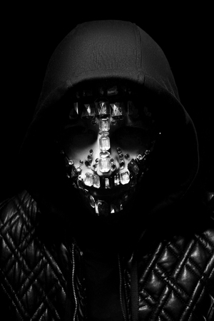 Art portrait of a hooded man with big rhinestones on his face. Mysterious mystical appearance of a man. Big crystals glisten in the dark on the guy face. Blurred out of focus Stock Photo