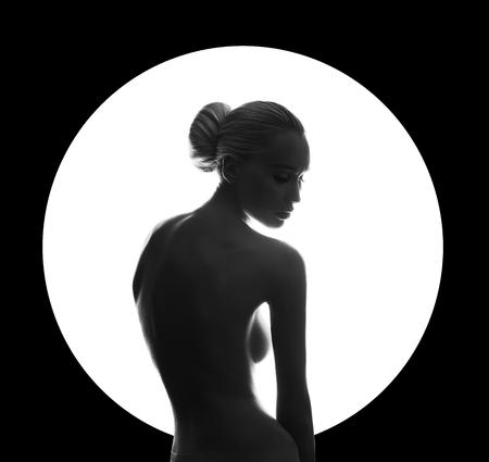 Kunst schoonheid Naakte vrouw op zwarte achtergrond in witte cirkel ring. Perfect lichaam, slank figuur, mooie borsten. Naakt mode vrouw poseren sensuele look perfecte make-up. Kunst van Stockfoto