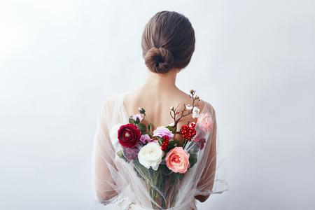 Femme avec un bouquet de fleurs artificielles derrière elle. La fille dans une robe transparente légère avec un dos ouvert et des fleurs. Portrait d'art d'une femme pour la couverture du livre Banque d'images