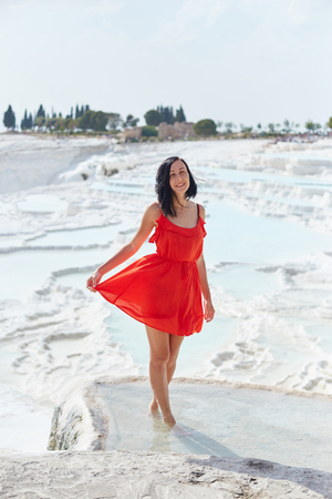 Girl in red dress on white travertines, Pamukkale Stock Photo