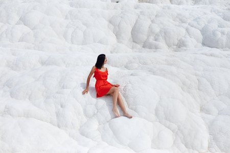 Girl in red dress on white travertines, Pamukkale Imagens