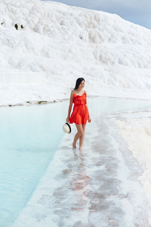 Girl in red dress on white travertines, water Stock Photo - 124957435