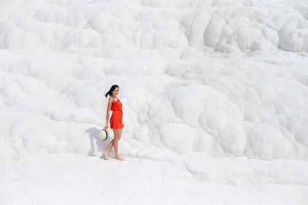 Girl in red dress on white travertines, Pamukkale Stock Photo - 124957442