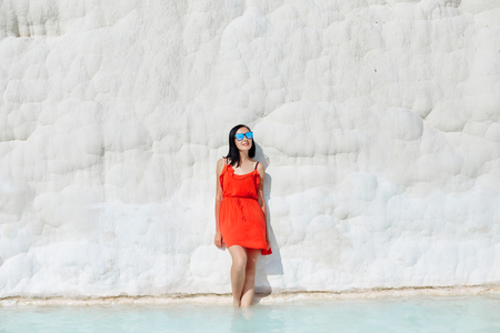 Girl in red dress on white travertines, water Stock Photo - 124957462