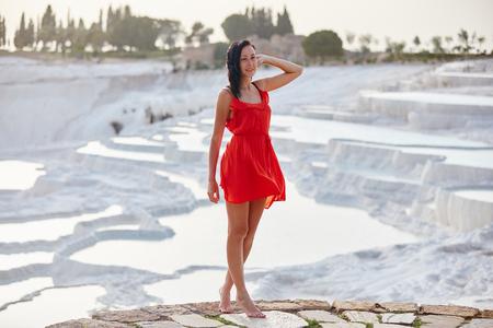 Girl in red dress on white travertines, Pamukkale Stock Photo - 124957464