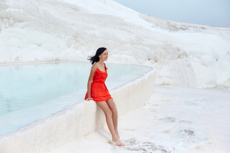 Girl in red dress on white travertines, water