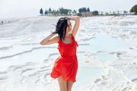 Woman in a red dress stands on white travertines. Girl in the sun near the white wall. Pamukkale