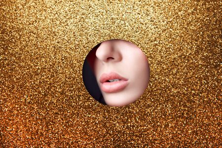 Beauty face red makeup plump lips of a young girl in a round slit hole of yellow gold paper. Woman with beautiful makeup plump lips, face in Golden slits circle hole